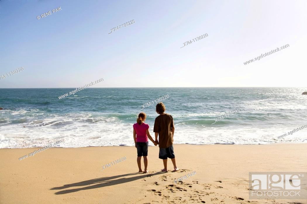 Stock Photo: Boy and girl looking out contemplatively at the vast ocean as the sun begins to set in Santa Cruz, California.