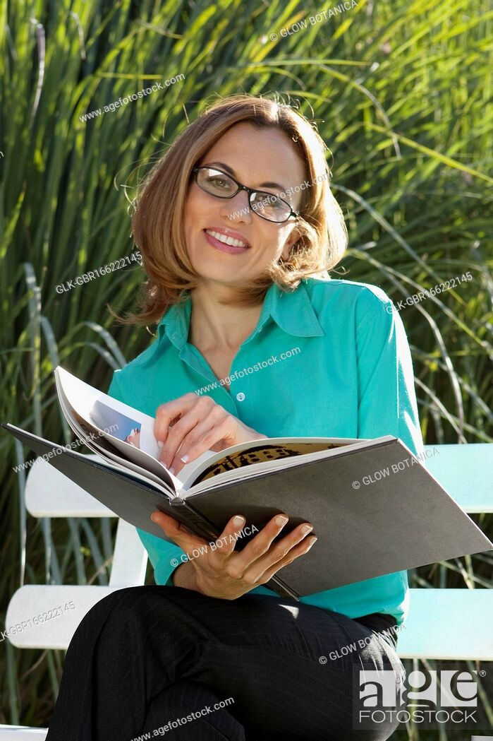 Stock Photo: Businesswoman reading documents in the park.