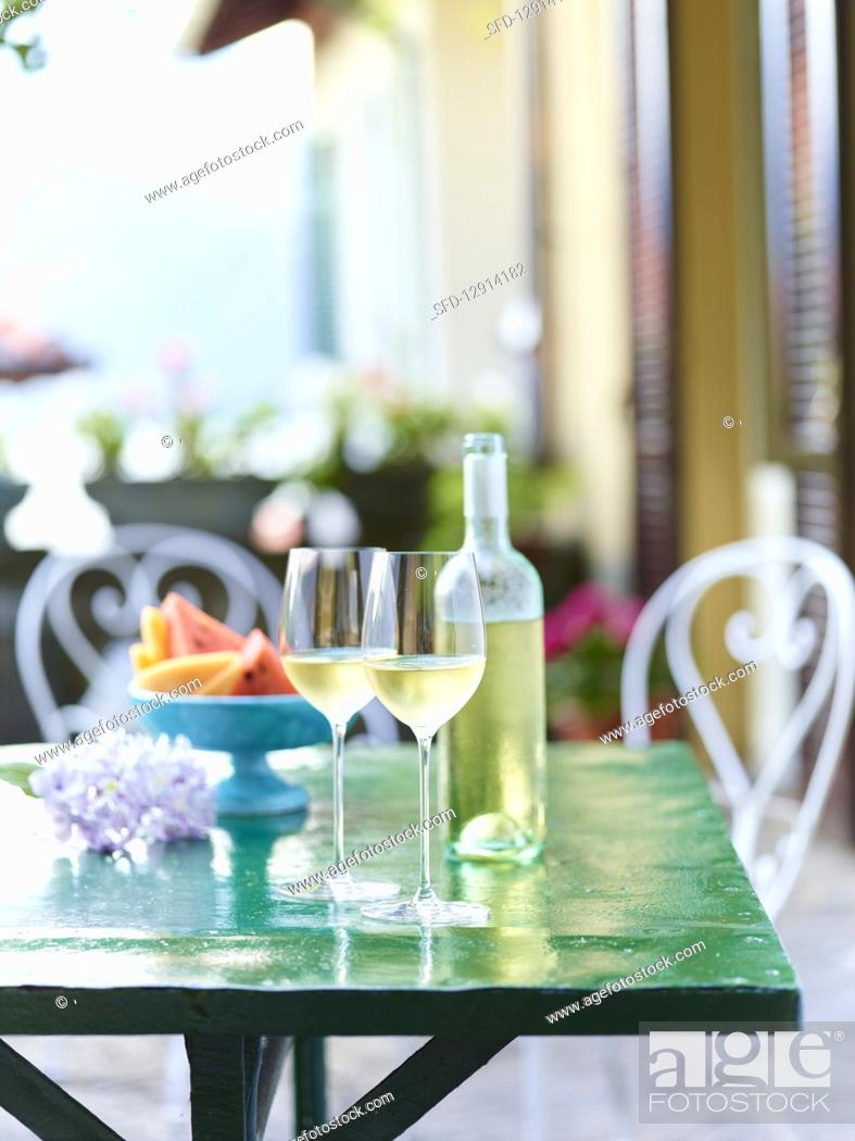 Stock Photo: Cold white wine in glasses and a bottle on a green table.