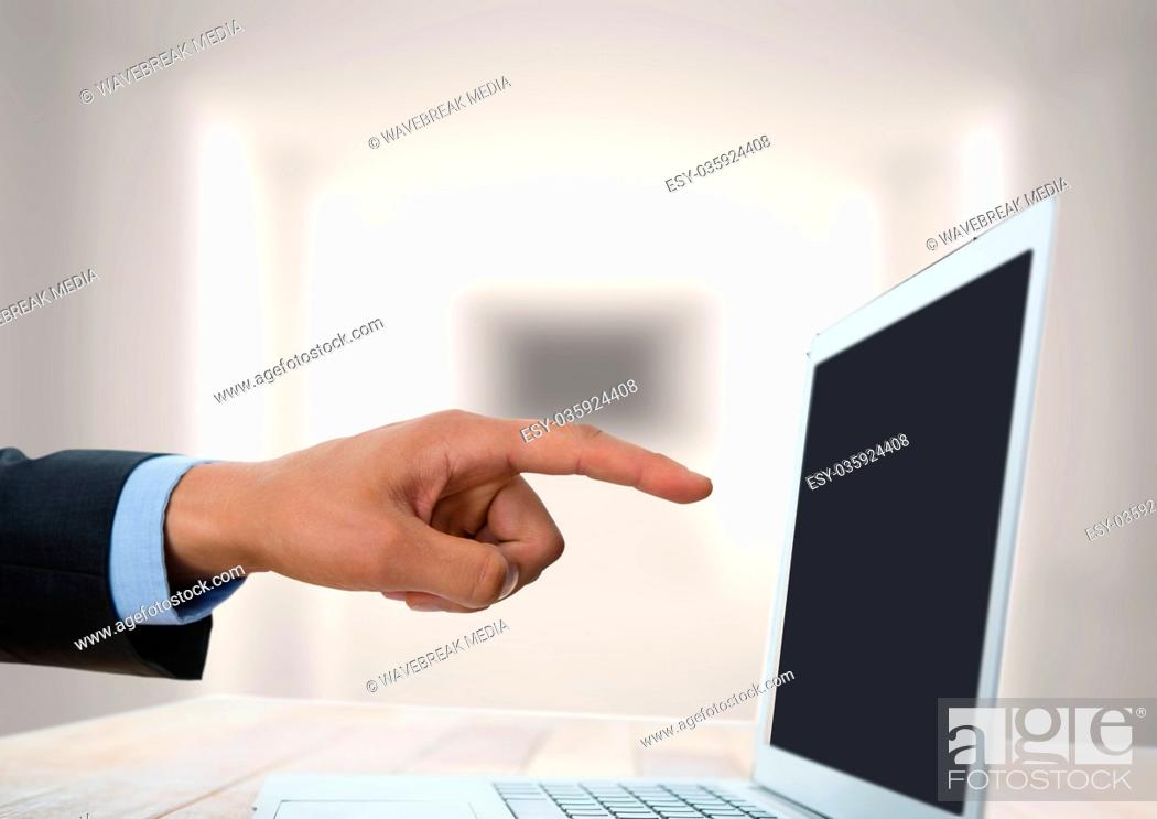 Stock Photo: Hand pointing at laptop with bright background.