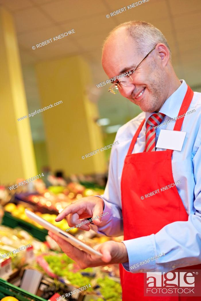 Stock Photo: Germany, Cologne, Mature man using digital tablet in supermarket.