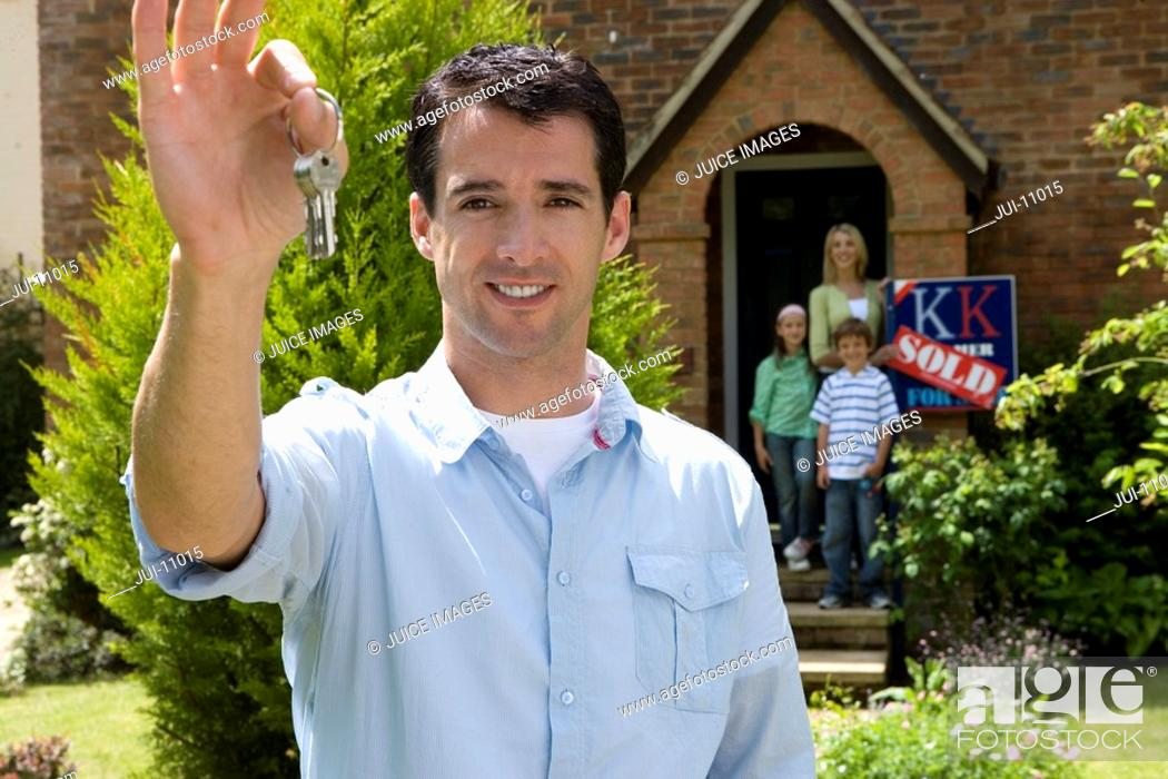 Stock Photo: Young man outside house holding up key, family in doorway in background, portrait.