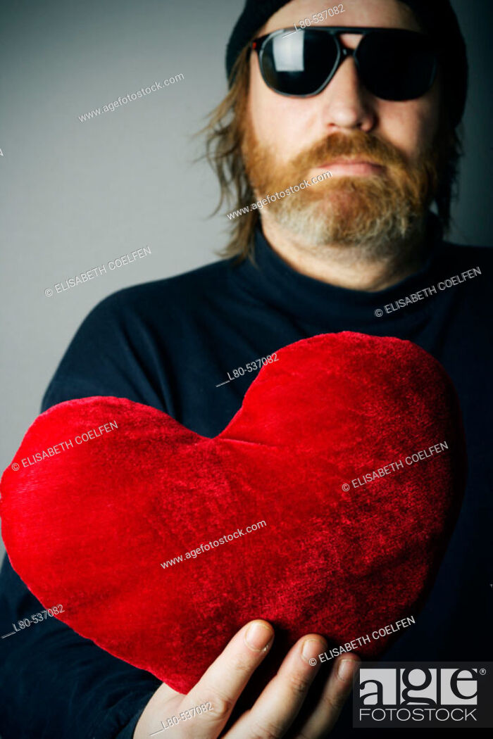 Stock Photo: Man holding red heart pillow.