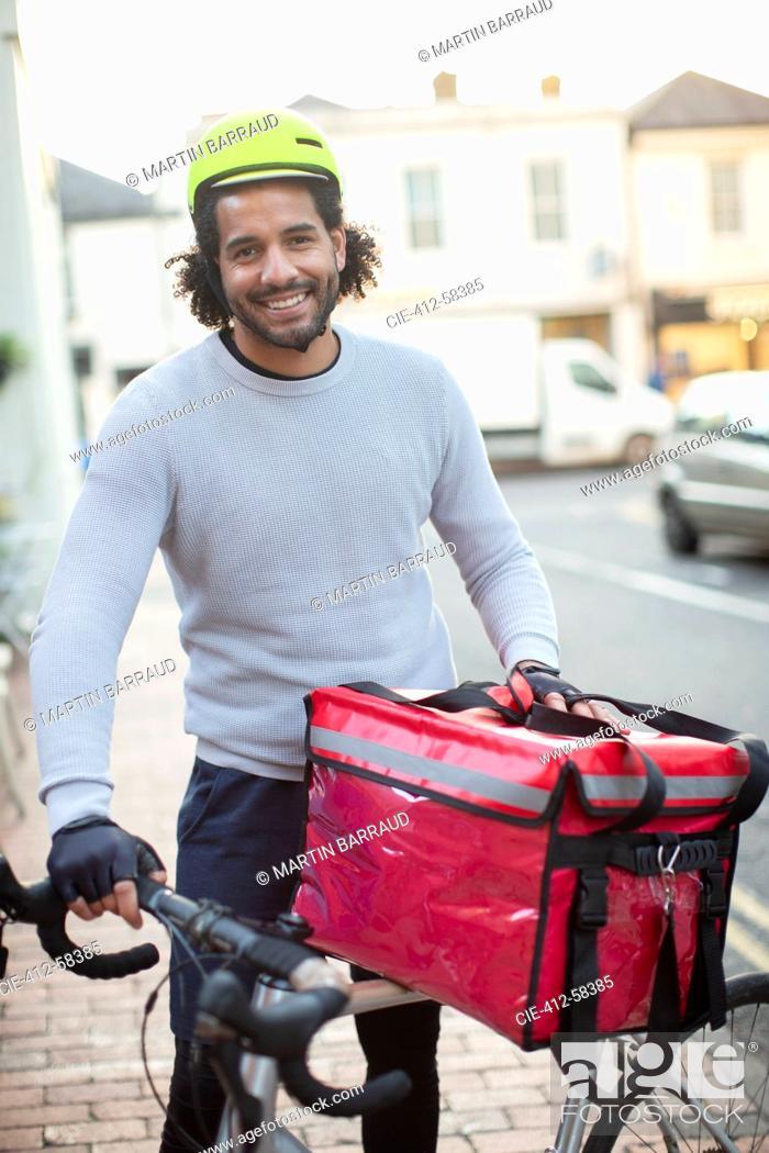 Photo de stock: Portrait happy young male bike messenger in helmet delivering food.