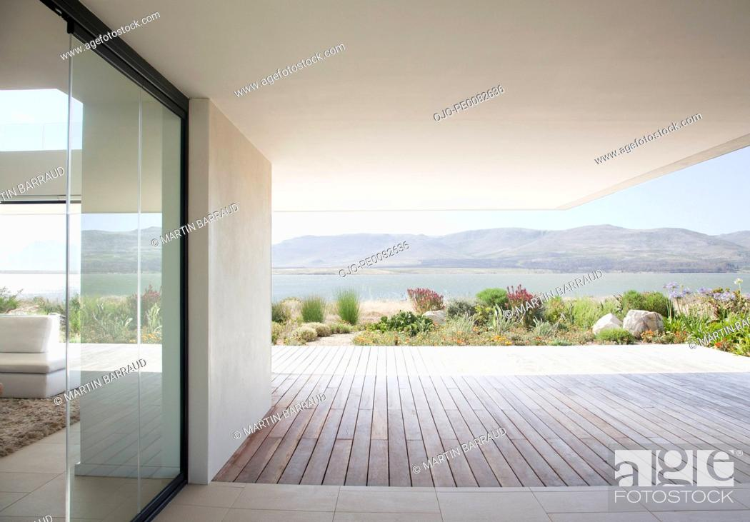 Stock Photo: View of lake from patio of modern house.