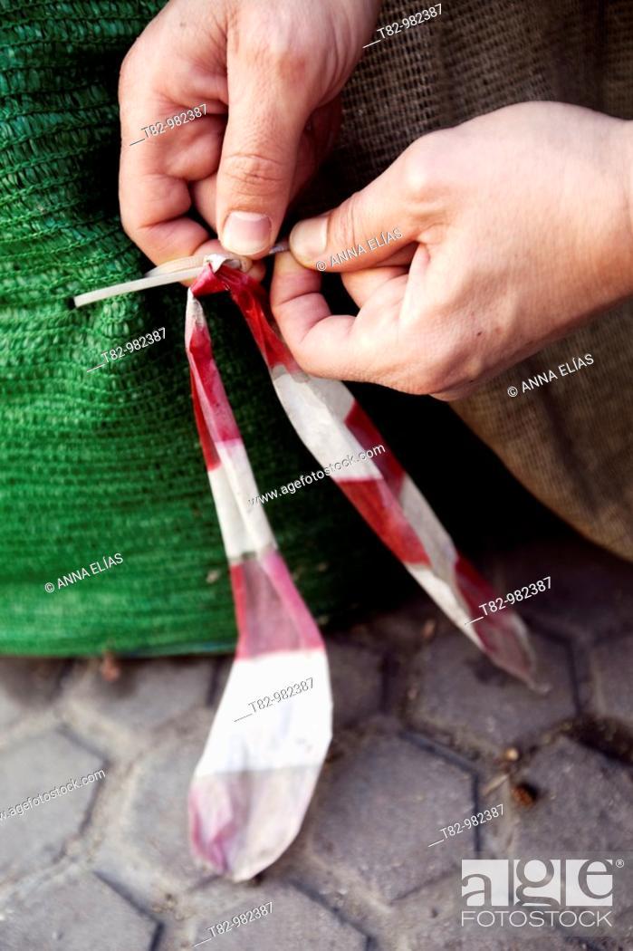 Stock Photo: manos de hombre manipulando una cinta de plastico blanca y roja,manos,human hands manipulating a white plastic tape and red hands.