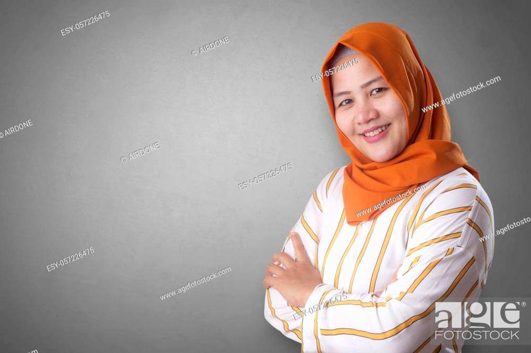 Stock Photo: Successfull happy Asian muslim woman wearing hijab smiling friendly with arms crossed, confident strong gesture.