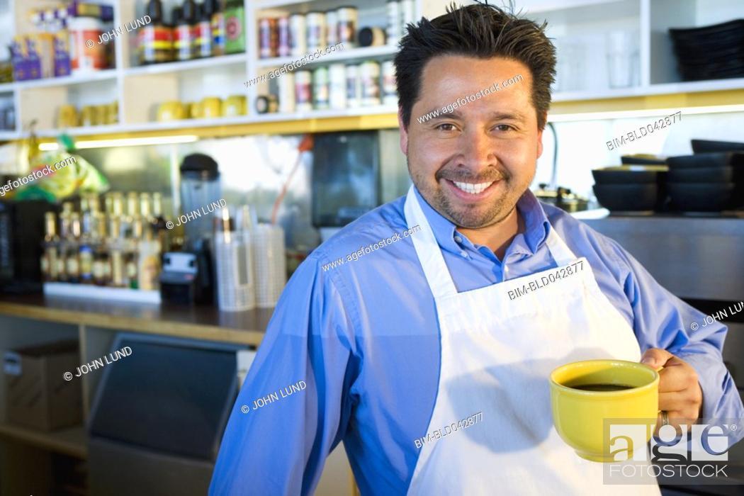Stock Photo: Hispanic cafe owner holding coffee mug.