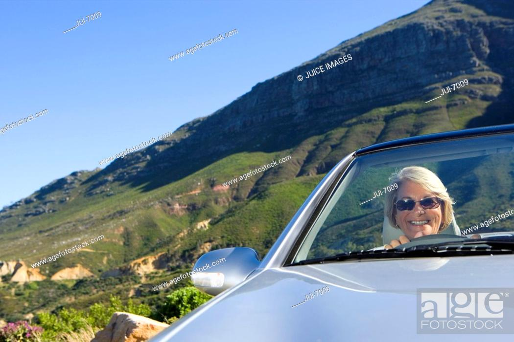 Stock Photo: South Africa, Western Cape, senior woman driving silver convertible car along mountain road, smiling, front view, portrait tilt.