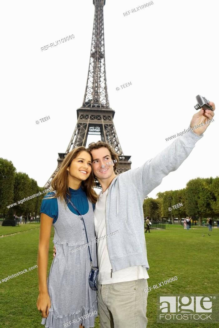 Stock Photo: Young couple in front of Eiffel tower, man taking photo, Paris, France.