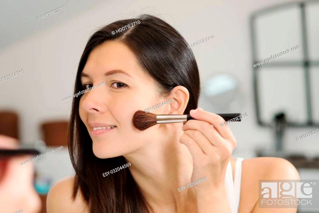 Stock Photo: Attractive smiling woman with her long brunette hair applying makeup in a mirror leaning forwards to see better as she applies blusher with a large soft.