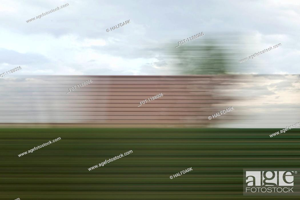 Stock Photo: A building and sky in blurred abstract pattern seen from moving train.
