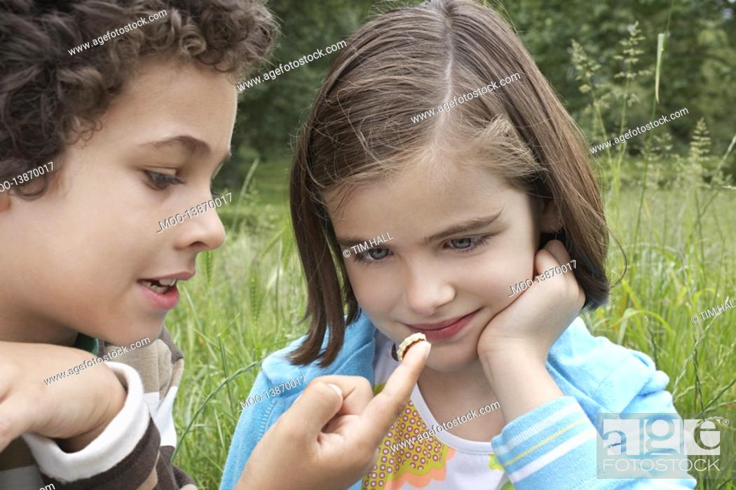 Stock Photo: Brother and sister 7-9 examining caterpillar in field.