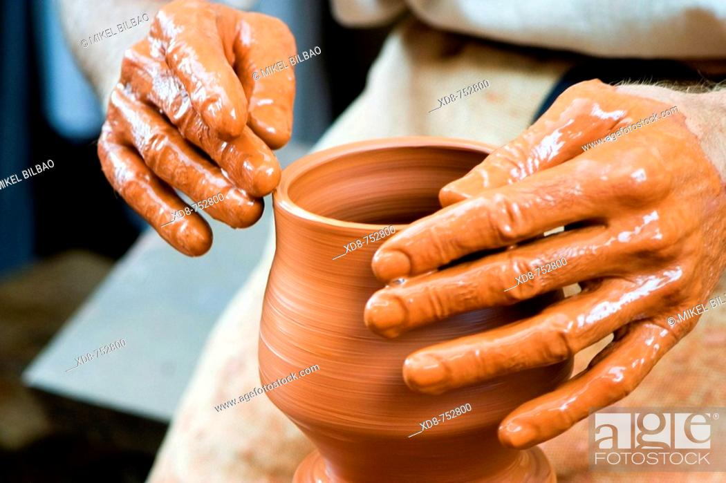 Stock Photo: Potter working in a clay pot.