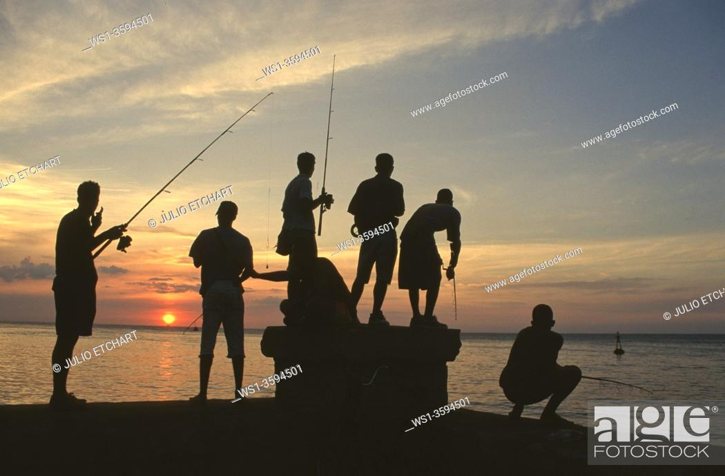 Stock Photo: Fishermen at sunset by the Malecón in Havana, Cuba.