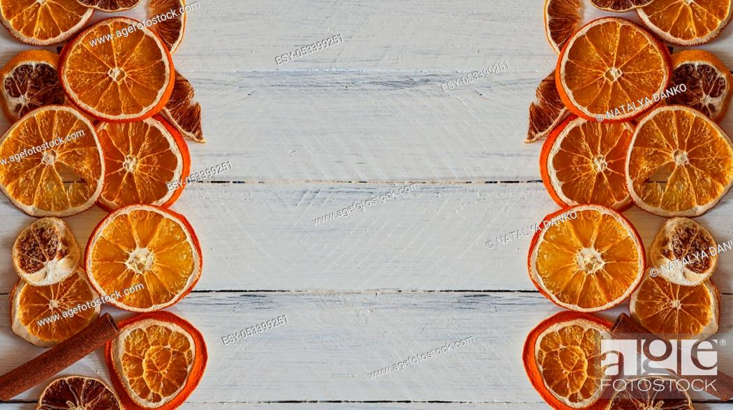 Stock Photo: slices of orange on a white wooden surface, empty space.