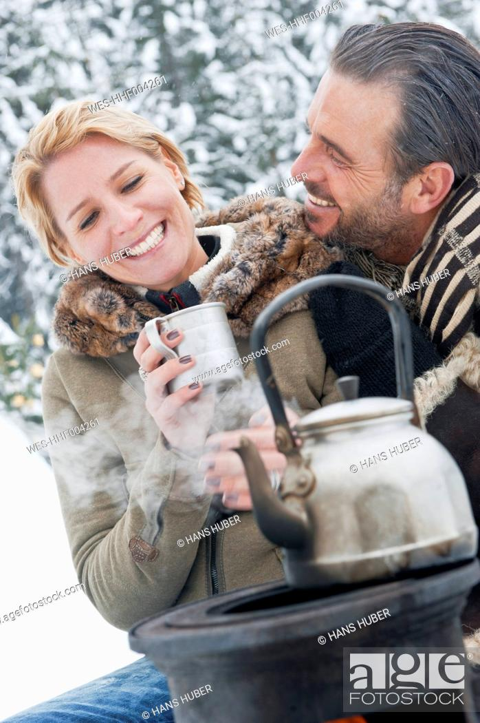 Stock Photo: Austria, Salzburg County, Couple sitting near camping stove, smiling.