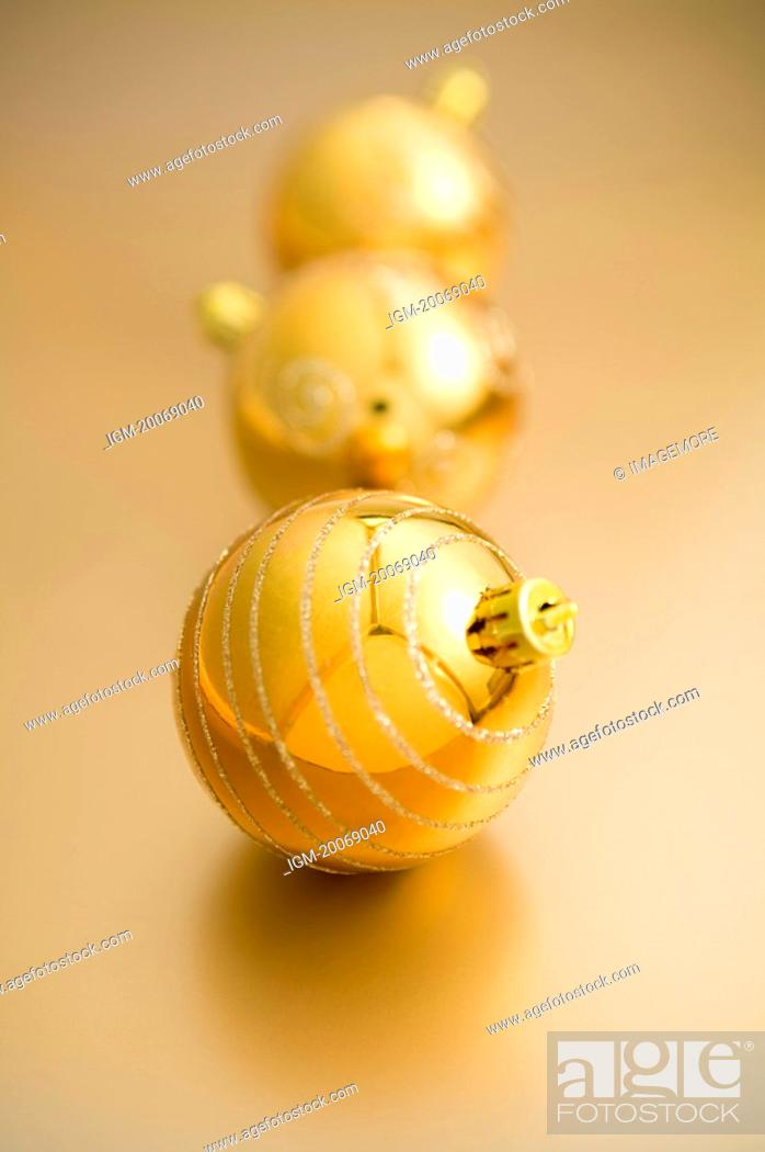 Stock Photo: Three golden Christmas baubles.