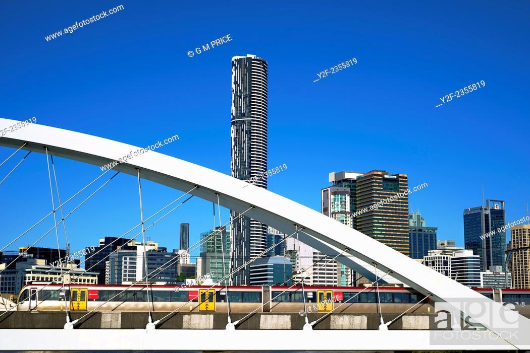 Stock Photo: suburban train crossing railway bridge over Brisbane River, with city skyline, Australia.