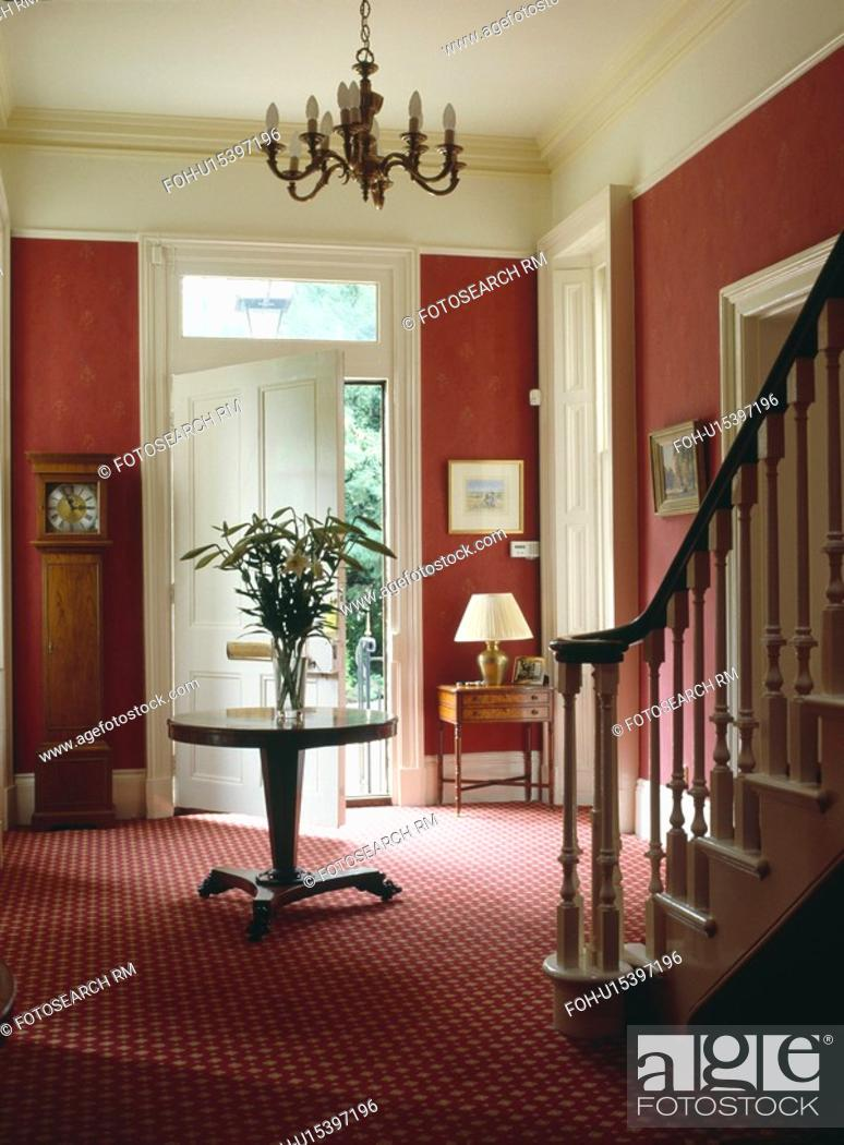 Stock Photo: Antique circular table and patterned red carpet in red country hall.