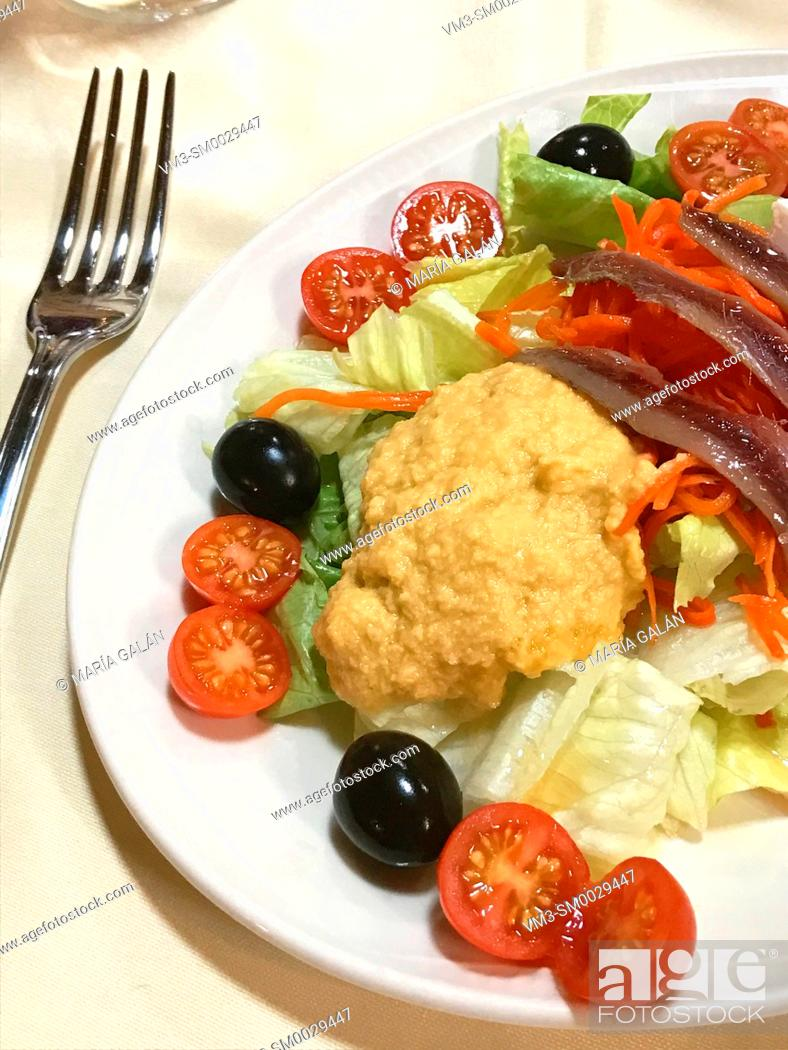 Stock Photo: Salad made of hummus, anchovy fillets, cherry tomatoes, black olives, carot and lettuce.