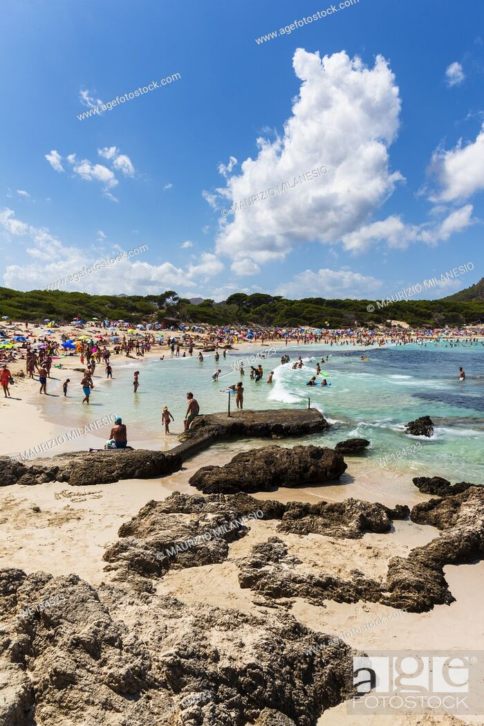 Stock Photo: Mallorca, Spain, August 14 2019: view of the beach and the rocks of Cala Agulla Majorca Spain with many tourists.