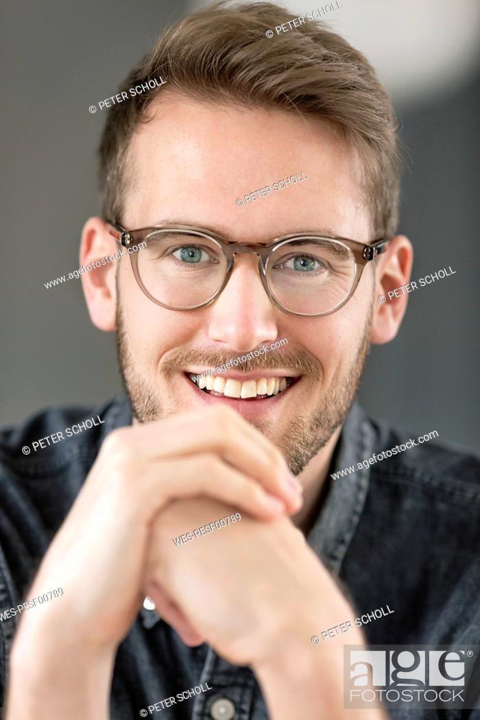 Stock Photo: Portrait of smiling young man with glasses.