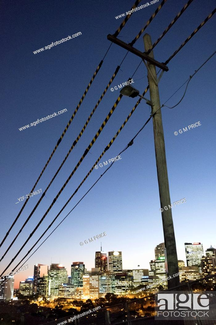Stock Photo: pole and protected power lines with view of North Sydney lights.