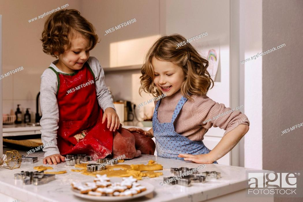 Stock Photo: Two happy girls preparing Christmas cookies in kitchen.