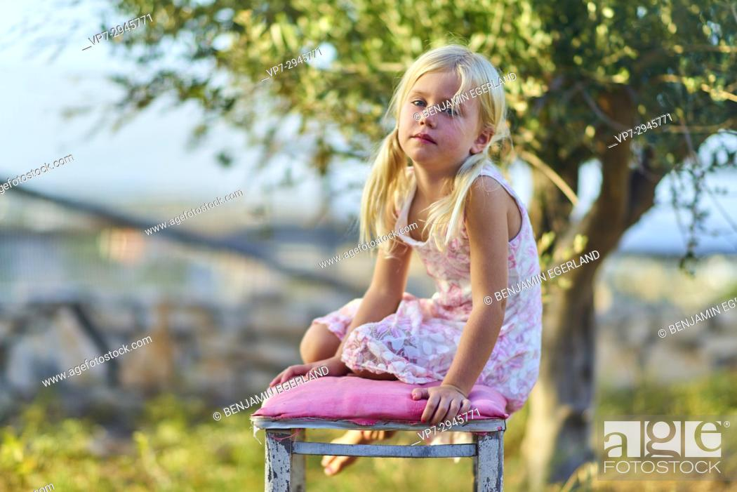 Imagen: young infant girl sitting on chair outside in nature garden. Australian ethnicity. During holiday stay in Hersonissos, Crete, Greece.