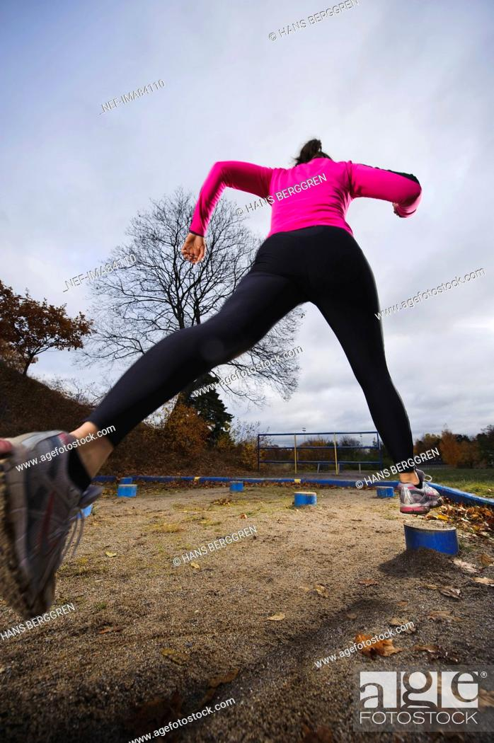 Woman jumping from one log to other, Stock Photo, Picture