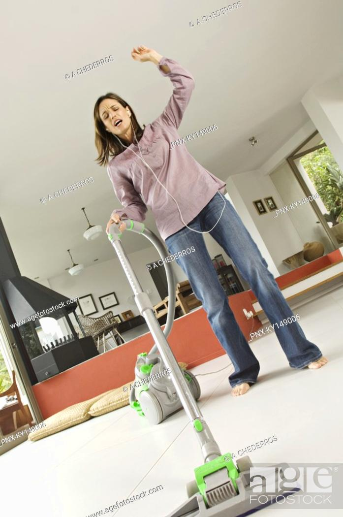 Stock Photo: Woman vacuuming while listening to MP3 player.