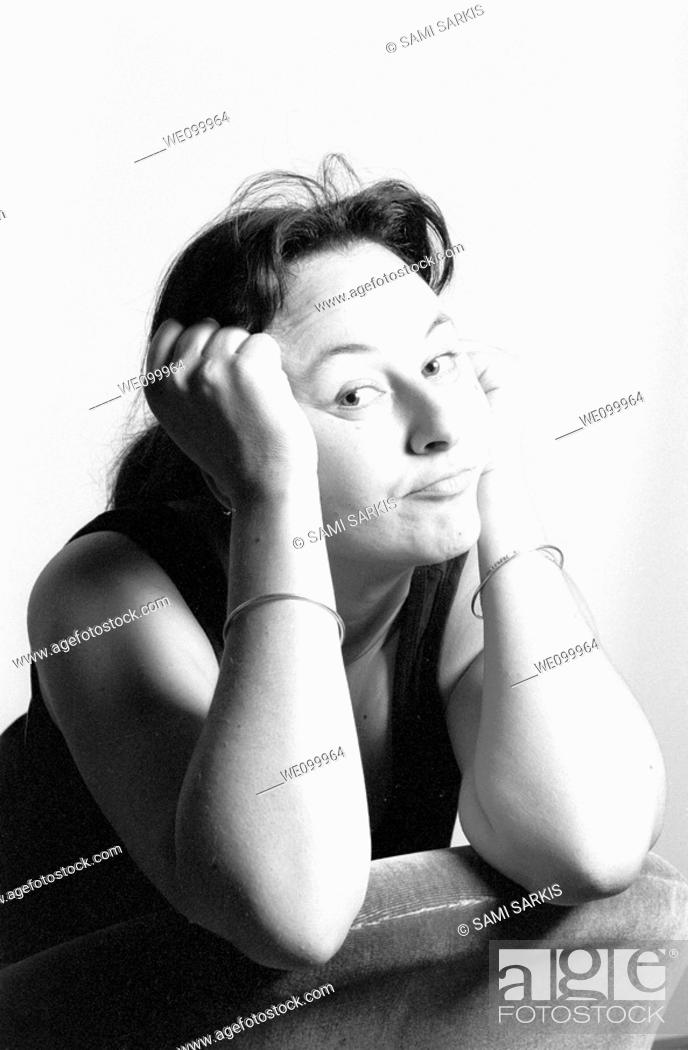 Stock Photo: Portrait of a woman looking bored with her head in her hands.