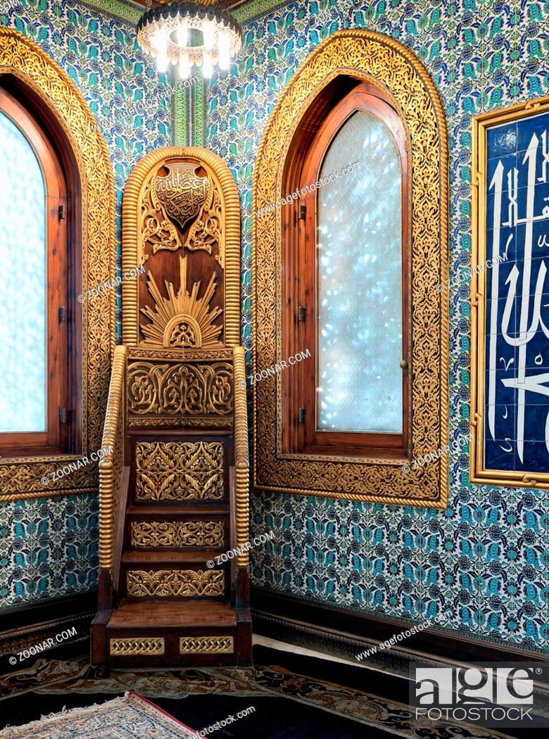 Stock Photo: Golden ornate minbar, wooden arched window framed by golden ornate floral pattern, and floral blue pattern ceramic tiles wall at the public mosque of Manial.