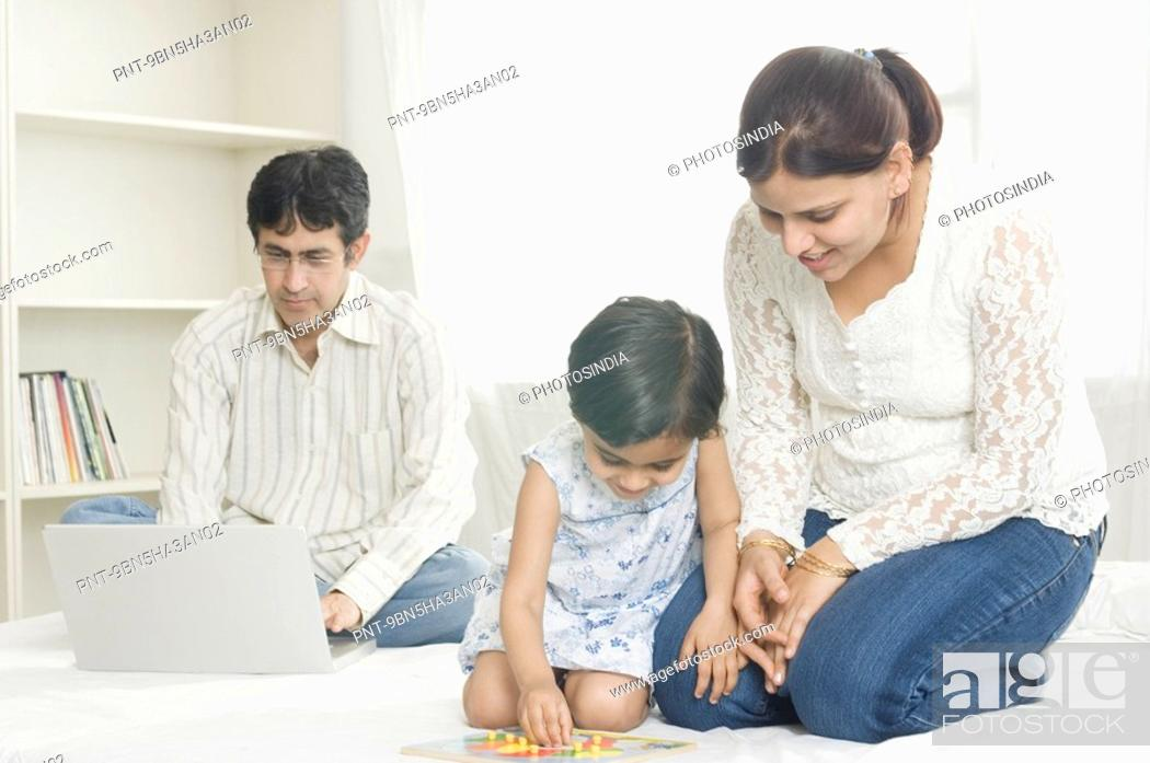 Mid Adult Woman And Her Daughter Playing A Board Game With A Mid Adult Man Using A Laptop Behind Stock Photo Picture And Royalty Free Image Pic Pnt 9bn5ha3an02 Agefotostock