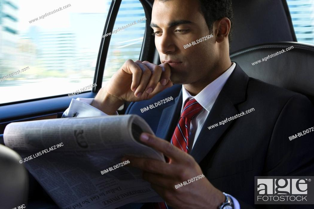 Stock Photo: Hispanic businessman reading newspaper in limousine.