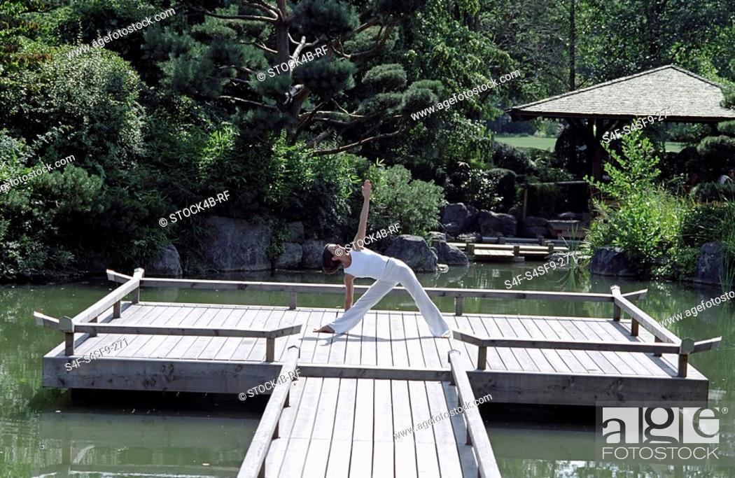 Stock Photo: Woman doing a Yoga-Exercise on a wooden Footbridge - Trees - Nature - Harmony.