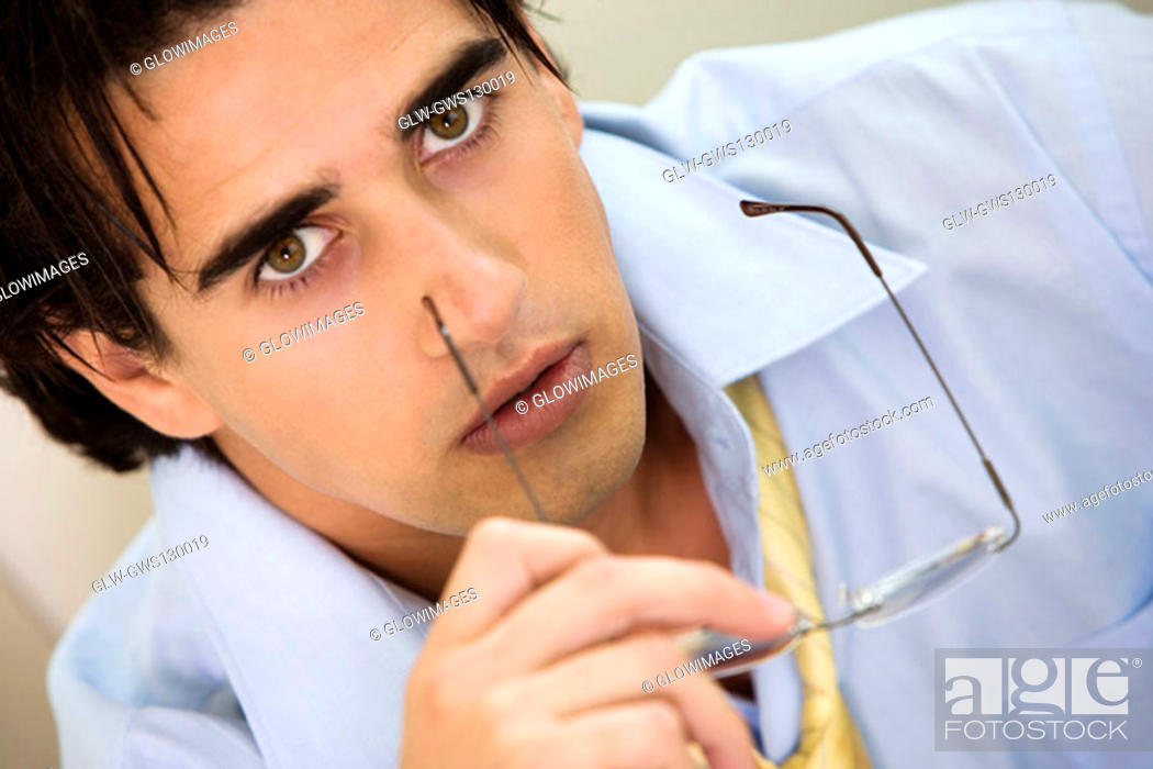 Stock Photo: Portrait of a businessman holding a pair of eyeglasses.