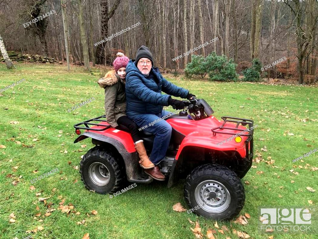 Stock Photo: Litle girl is riding on a quad with her father, they are both looking at the camera.