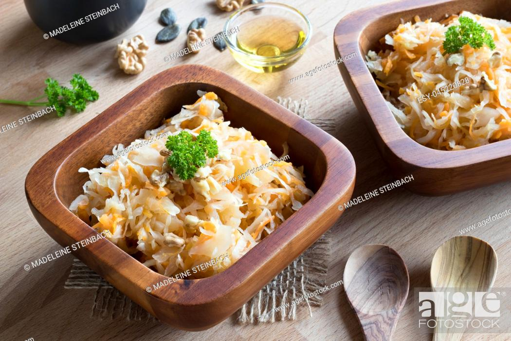 Stock Photo: Fermented cabbage and carrots in two wooden bowls on a wooden table, with walnuts, parsley and pumpkin seeds in the background.
