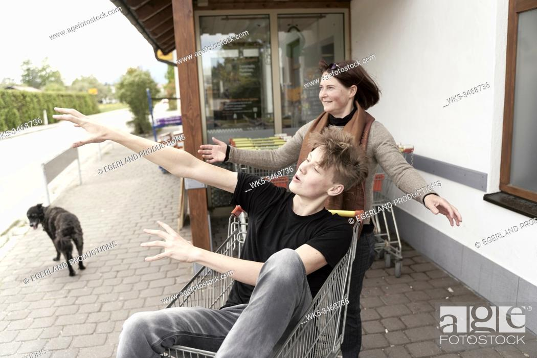 Imagen: Mother and son fooling around with a shopping cart, in Gaissach, Bavaria, Germany.