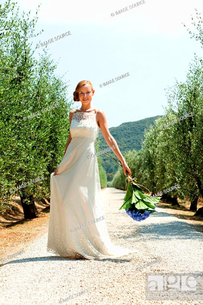 Stock Photo: Bride on country road holding bouquet.