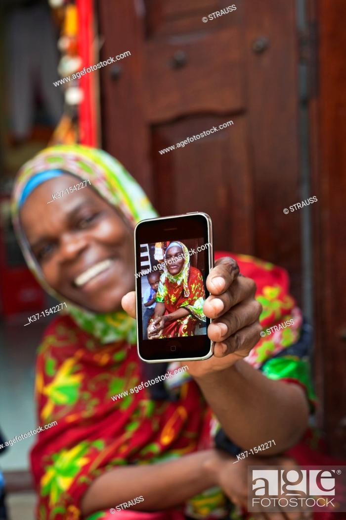 Stock Photo: Local woman in East African market and holding smart phone with her photo.