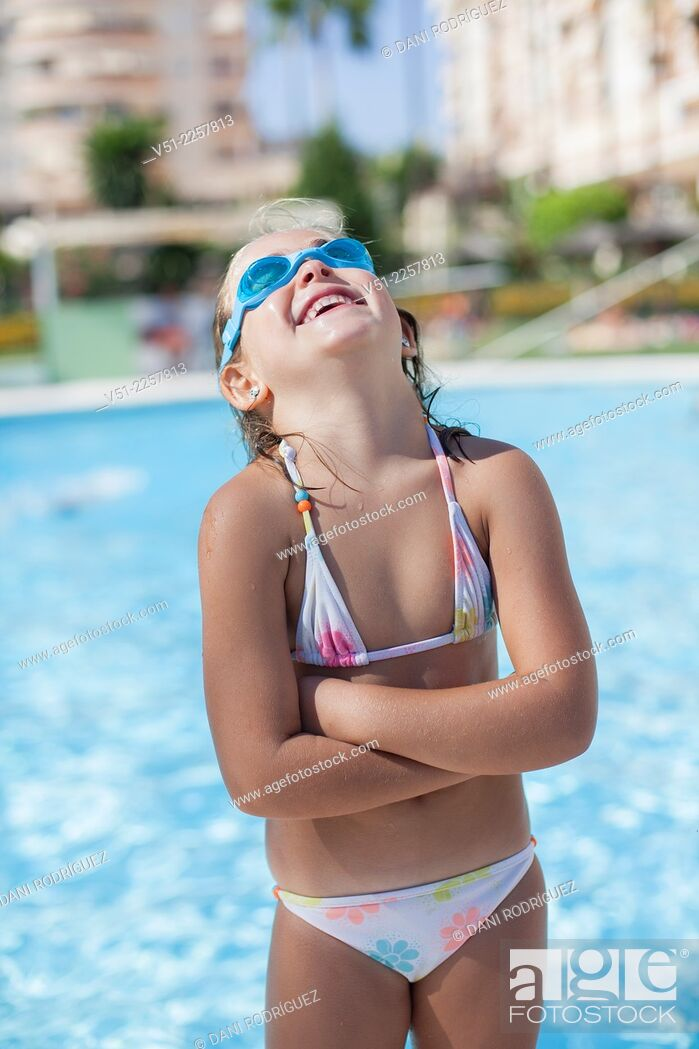 Stock Photo: Pretty young girl in swimming pool laughing with Swim Goggles.