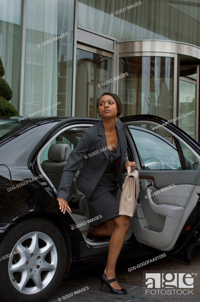 Stock Photo: Businesswoman emerging from backseat of expensive car.