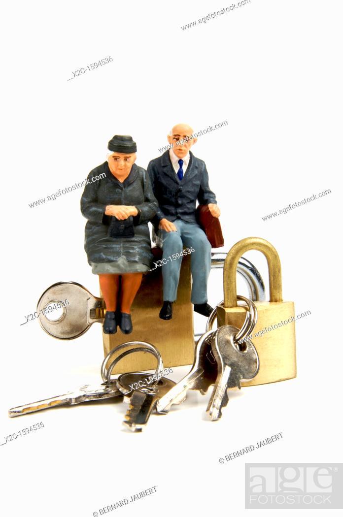 Stock Photo: Miniature figurines of elderly couple sitting on padlocks.