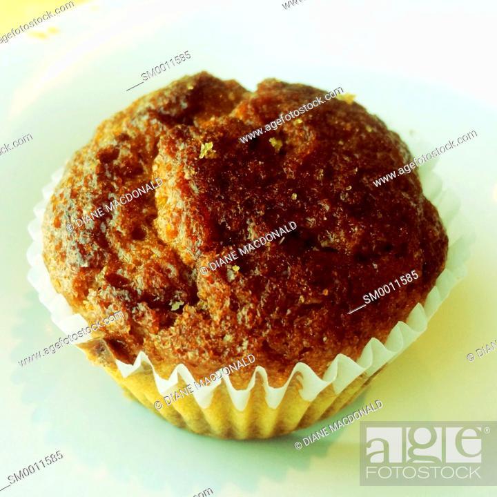 Stock Photo: A healthy raisin bran muffin on a white plate.