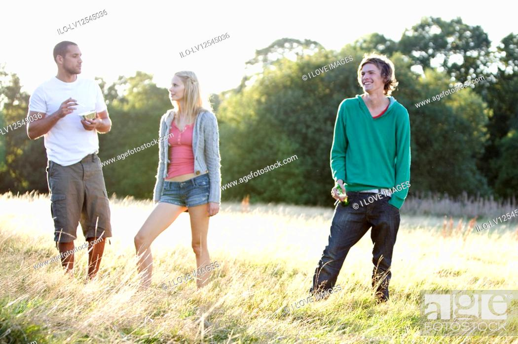 Stock Photo: Three young friends standing in a field, one eating.