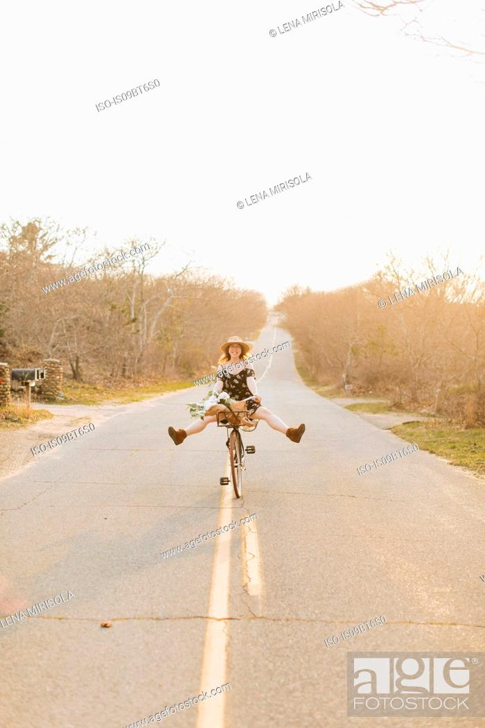 Photo de stock: Young woman riding bicycle with legs raised on rural road, Menemsha, Martha's Vineyard, Massachusetts, USA.