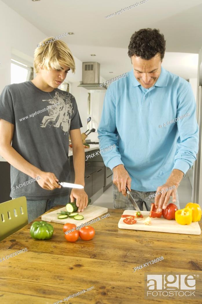Stock Photo: Faher and teenager cooking, indoors.